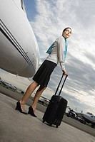 Side profile of a cabin crew standing and holding her luggage near a private airplane