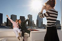 Woman taking picture of young couple on boat