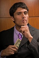 Young businessman with finger over mouth stealing money (thumbnail)