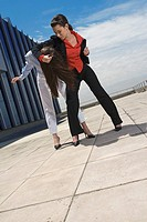 Businesswomen on roof fighting and pulling hair