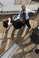 High angle view of businesspeople fighting near ledge of roof