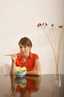 Young woman eating with chopsticks