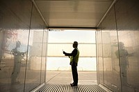 Side profile of a businessman holding a clipboard in a cargo container