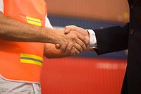 Mid section view of a businessman shaking hands with a male dock worker