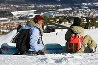 Rear view of two people sitting on snow with snowboards