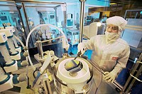MEMS production. Clean room technician using photolithography processes to produce MEMS microelectromechanical systems devices. MEMS devices are const...