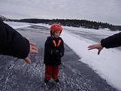 Parents reaching ice skating to their son, Sweden