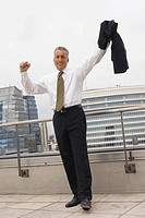 Happy mature businessman standing on roof