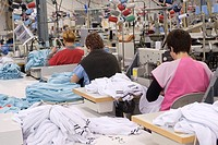 Textile industry. Workers using sewing machines to assemble the final clothing products from piles of mass_produced fabric templates. This factory, ru...