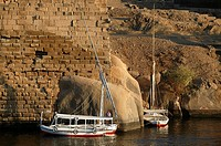 Felouques and motorboat lying at the foot of the Elephantine Island on the Nile close to granite rocks