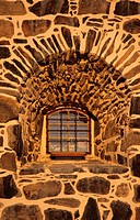 Closeup view of stone wall with arched window