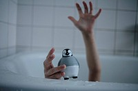 Close_up of a child´s hand holding toy in a bathtub