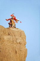 Blackfoot Blood Plains Indians man on a cliff in traditional mens fancy dance outfit, Indian Battle Provincial Park, Lethbridge, Alberta, Canada.
