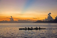 Outrigger canoe at sunset off the island of Tahiti. The blue band in the sky is believed to be the shadow cast from a mountain on a distant island.