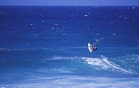USA, Maui _ Male windsurfing in large surf waves.