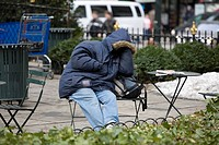 Homeless man taking a nap in Bryant Park in New York City.