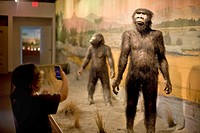 A seven_year_old boy taking a picture with an iPhone of prehistoric men in Las Vegas´ Natural History Museum.