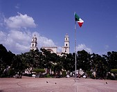 central Square Merida Yucatan Peninsula Mexico Blue sky Clouds Tree Green People Square Flag