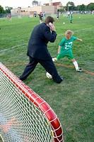 Multitasking dad in business suit talking on cell phone and playing soccer  Carondelet Field Expo School St Paul Minnesota USA