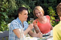 Young couple drinking white wine at table out of doors