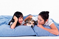 Mother and daughter with their Pembroke Welsh Corgi, all Lying in Bed Together, Front View