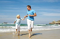 Man running with his son on beach