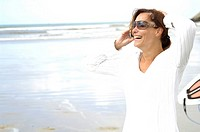 Close_up of woman talking on mobile phone on the beach