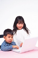 Girl and boy looking at the monitor of a laptop on the table, Smiling, Side View