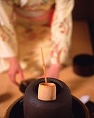 Woman in kimono setting up for tea ceremony, front view, Japan, differential focus