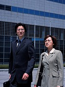 Businessman and businesswoman walking by the side of building, Front View