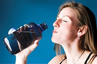 Female model drinking water from bottle