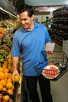 Caucasian mid_adult male grocery shopping for fruit