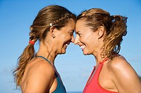Caucasian mid_adult women with heads together smiling