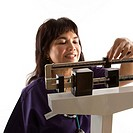 Middle_aged female Filipino nurse reading weight on scale