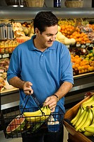 Caucasian mid_adult male grocery shopping for bananas