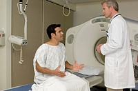 Portrait of adult patient sitting in front of cat scan with doctor