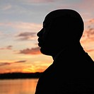 African_American man standing by water at sunset in Washington, D.C., USA