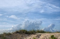 Sand dune with beach grass and cloudy sky