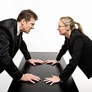 Caucasian mid_adult businessman and woman staring at each other with hostile expressions.