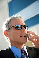 Close up side view of Adult Caucasian man in suit talking on cell phone in urban setting.