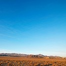Barren desert landscape with mountains in distance.