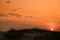 Sun setting over beach sand dune on Bald Head Island, North Carolina