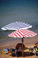 Umbrella and beach chairs on sand at waters edge