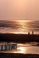 Sunset over beach, tide out, wooden posts in foreground with people Heacham UK