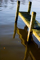 Wooden jetty on the Thames river and its reflection on the water