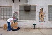 Man installing an art gallery in the street in Soho, Manhattan. NYC, USA