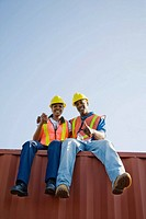 Workers sitting on cargo container