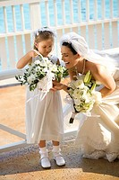 Caucasian mid_adult bride kneeling next to flower girl admiring her flowers.