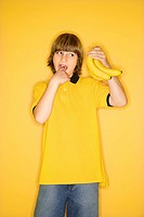 Portrait of Caucasian boy holding bunch of bananas and gesturing with finger in mouth that they are gross standing against yellow background.