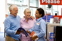 Mature couple shopping for computer, in conversation with saleswoman, smiling (thumbnail)